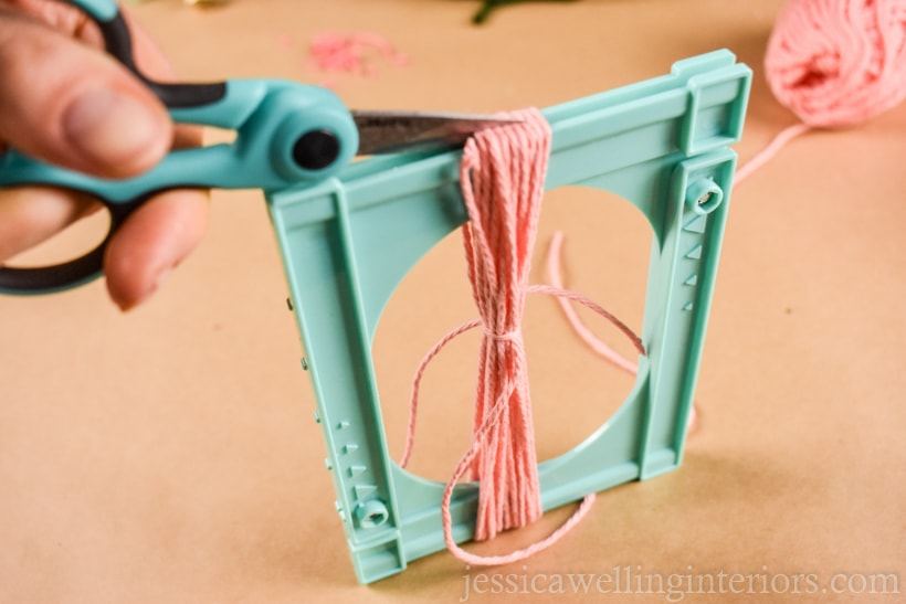 hands using scissors to cut yarn tassel ends