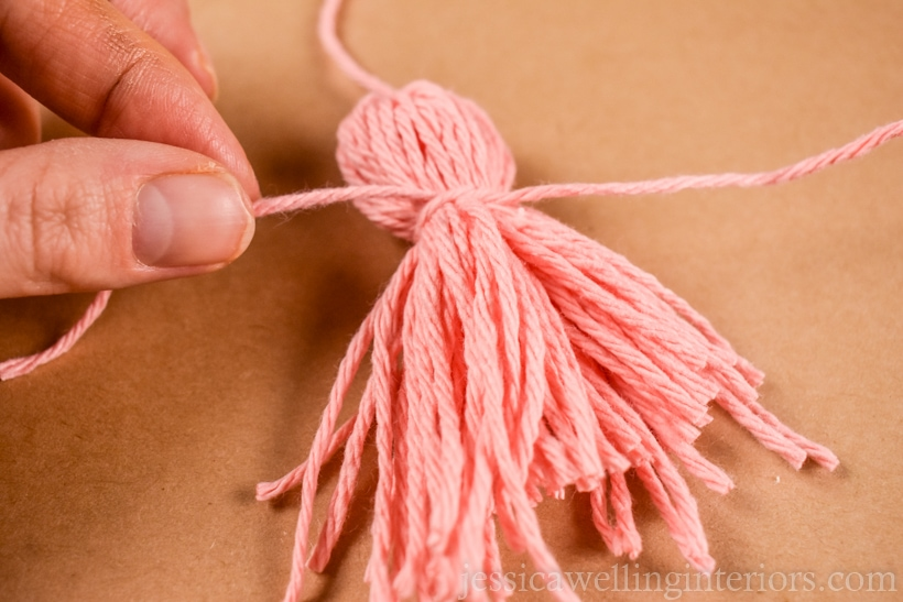 hand tying a pink yarn tassel around the center with another piece of pink yarn