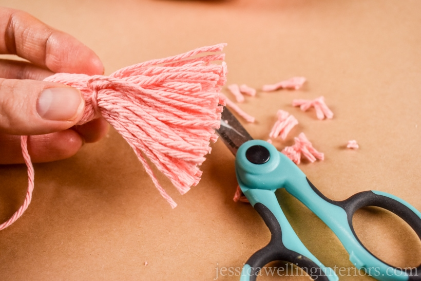 hand holding a small yarn tassel after the ends of yarn have been trimmed with scissors