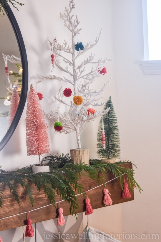 mantel decorated for Christmas with a Boho tassel garland, trees with colorful pom poms, etc.