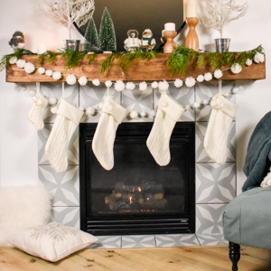 mantel decorated for Christmas with a pom pom garland and Christmas stockings