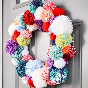 colorful pom pom wreath on a front door