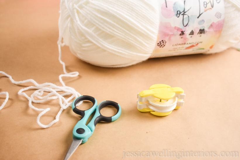 close-up of a skein of white yarn, a small yellow pom pom maker, and a pair of craft scissors