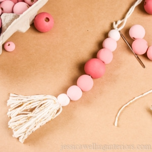 close-up of a pink wood bead Christmas ornament with a tassel on the end