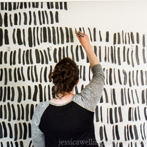 woman painting an accent wall with a brush stroke pattern in black and white