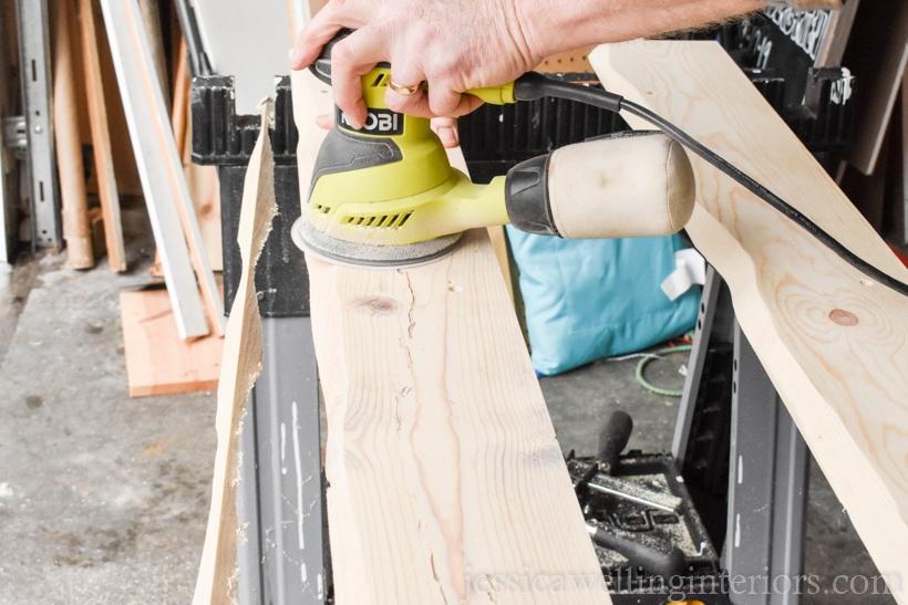 hand using an orbital sander to sand a wood coat rack before applying wood stain