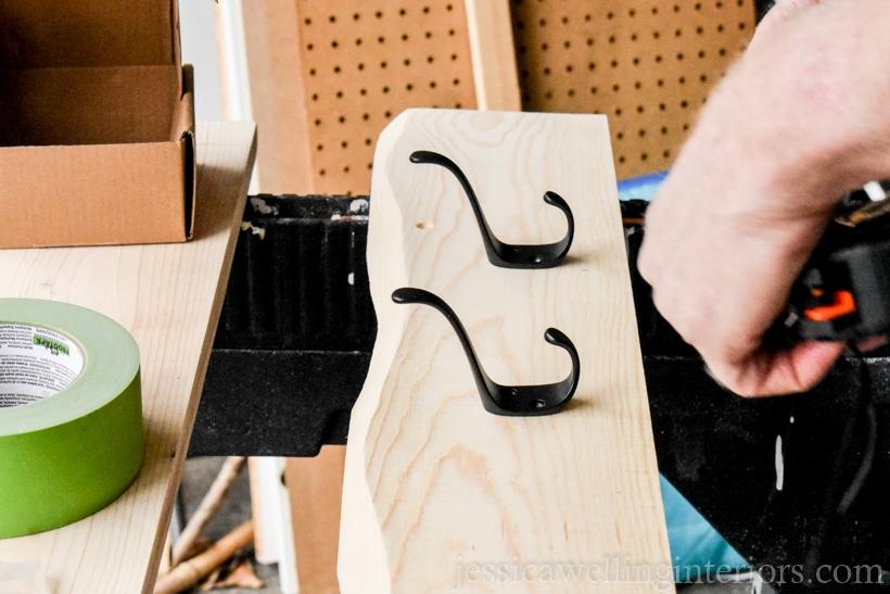wooden coat rack with 2 black metal hooks sitting on top