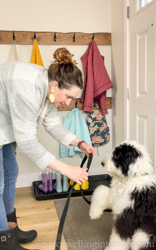 woman putting leash on a sheepadoodle puppy in a modern entryway with DIY wall hook racks behind her