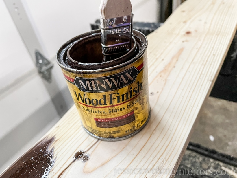 special walnut-colored wood stain being applied to an unfinished wooden coat rack