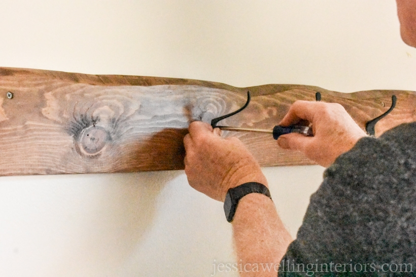 black metal wall hooks being attached to a wall-mounted coat rack