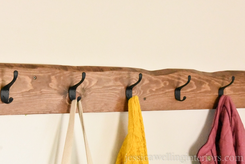 diy wall coat rack with a live edge and coats hanging from it