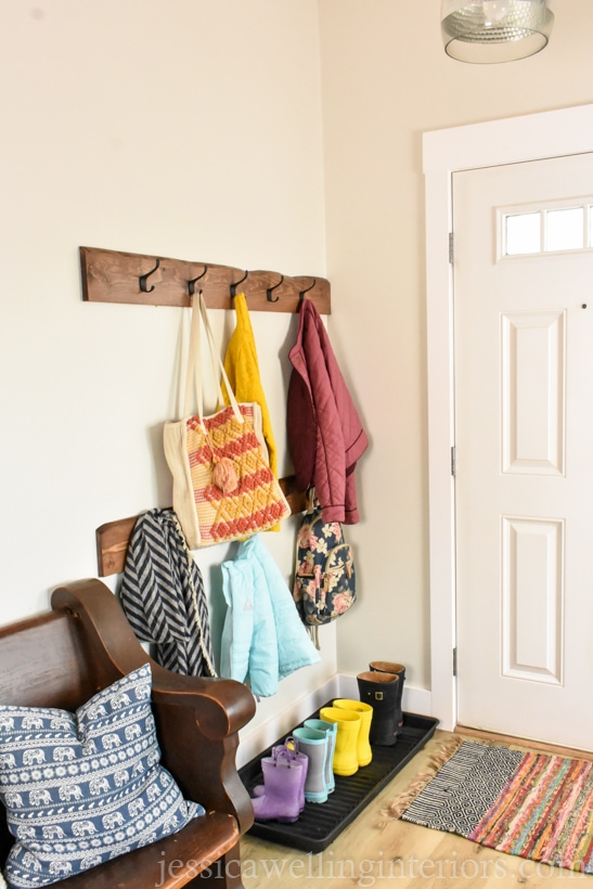 entryway with boot tray and rain boots lined up in it and live edge wood coat racks above it