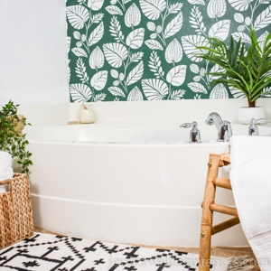 bathtub with green stenciled accent wall behind it