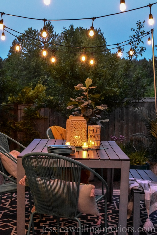 glowing patio lights hung from DIY conduit poles over an outdoor dining table