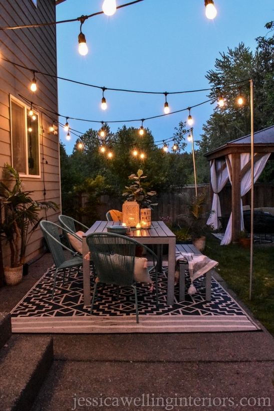 Boho patio with glowing string lights hung from DIY string light poles
