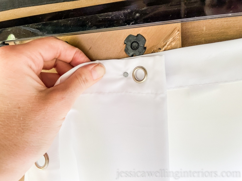 close-up of outdoor curtain panel being nailed to hang it up in an outdoor living room