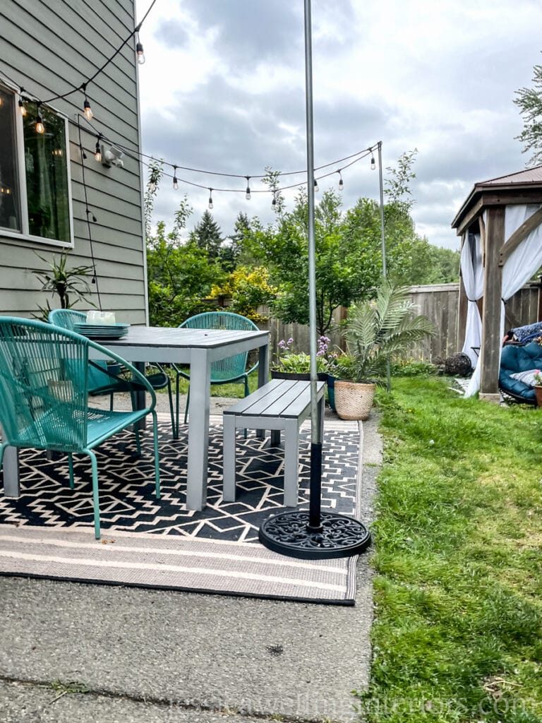backyard patio with simple DIY outdoor string light poles made from umbrella bases and electrical conduit