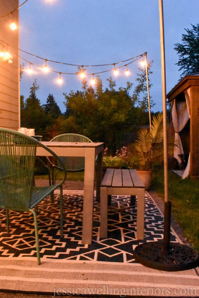 patio with an umbrella stand outdoor string light pole in the foreground