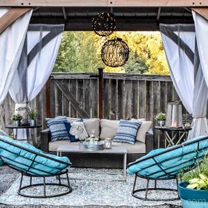 gazebo with outdoor papasan chairs, outdoor curtains, and lights