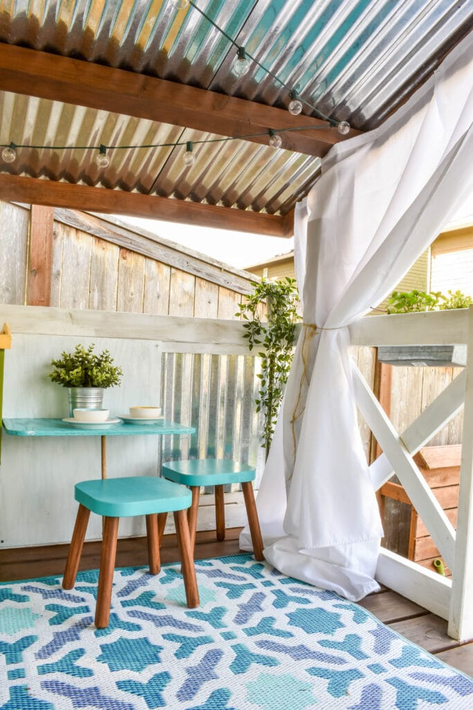 interior view of cute kids playhouse with diy outdoor curtains, an outdoor rug, a table and two Ikea Flisat stools
