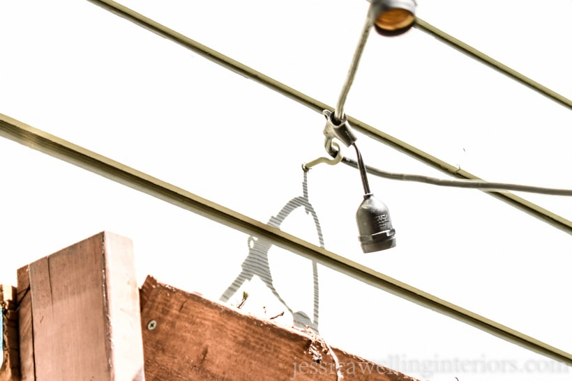 string lights attached to a cup hook mounted on the side of a house