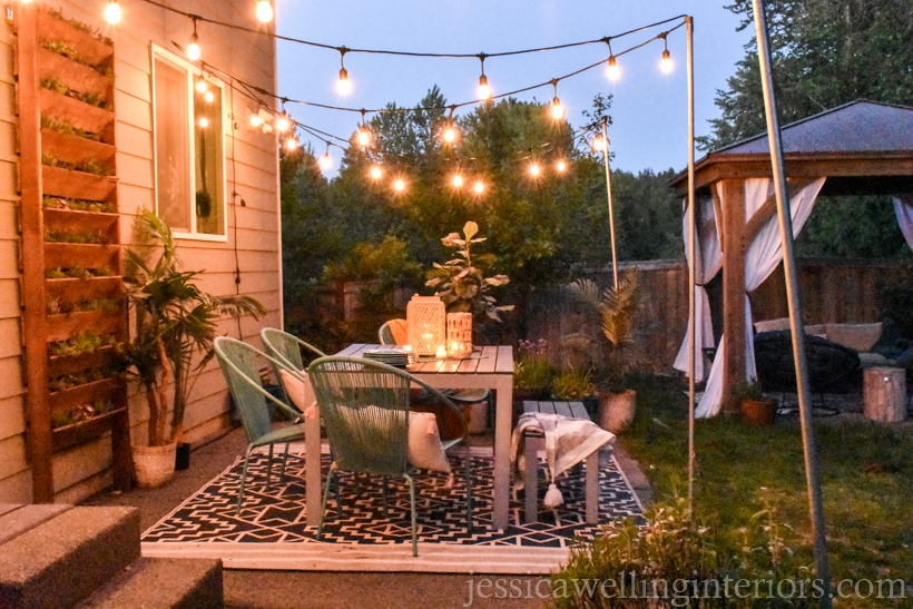 backyard patio lit with glowing string lights hung from DIY string light poles