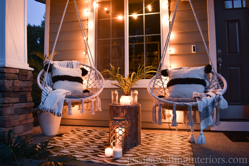 porch with glowing string lights draped over a window and two macrame swing chairs