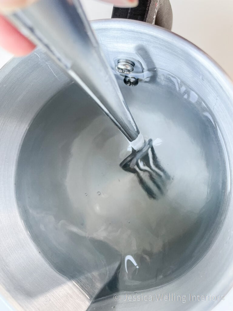 close-up of a pitcher of melted wax being stirred with a fork