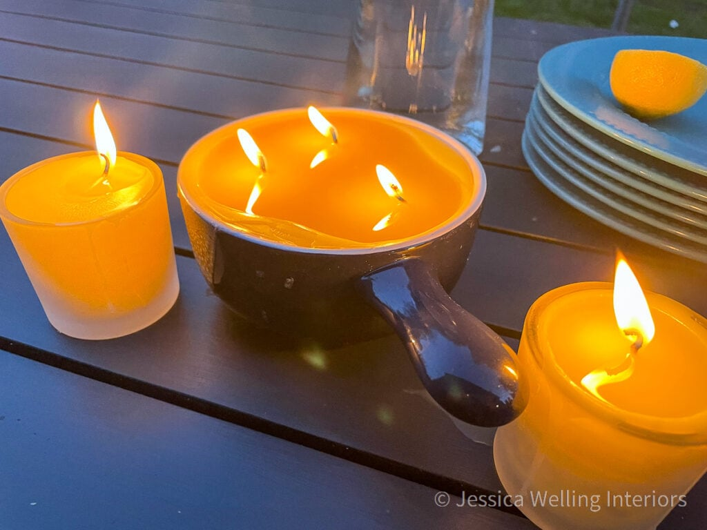 Citronella candles lit on a patio table