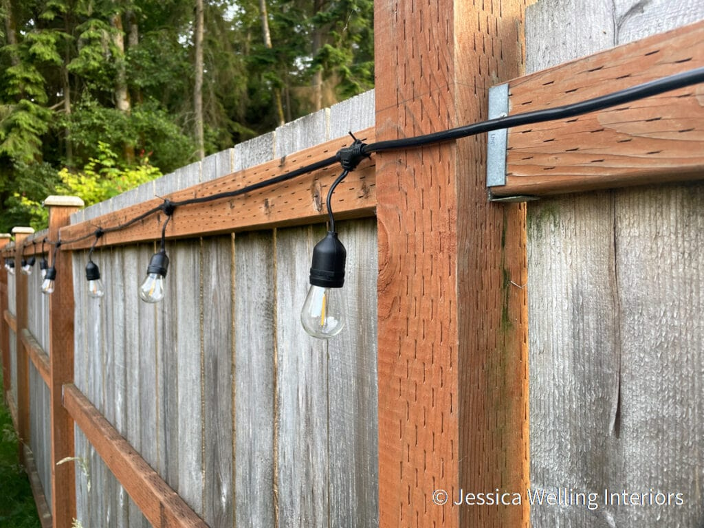 heavy-duty string lights attached to a fence with finish nails