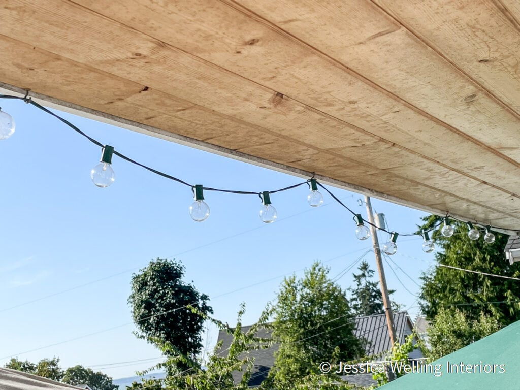 string lights attached to the underside of a deck roof with cup hooks
