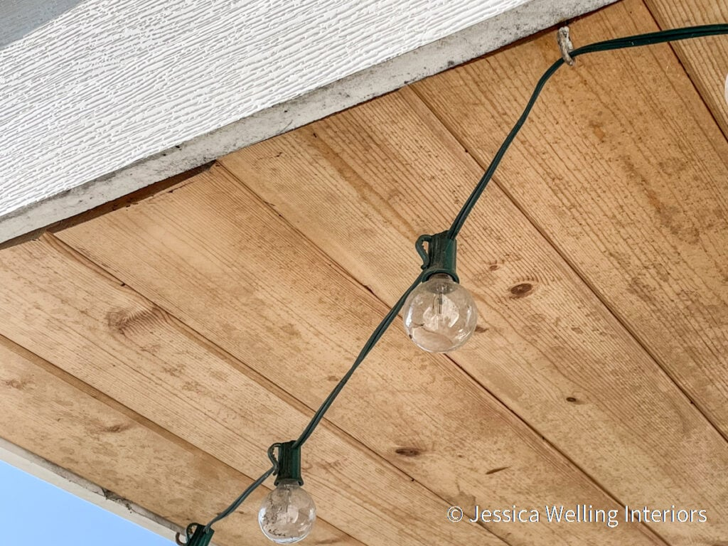 close-up of string lights attached to the underside of a roof with cup hooks