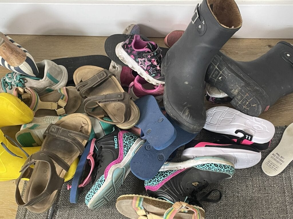 entryway with a big pile of shoes on the floor