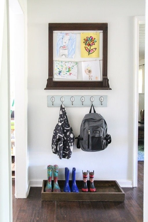 entryway nook with a wood boot tray and wall hooks with a child's backpack and coat