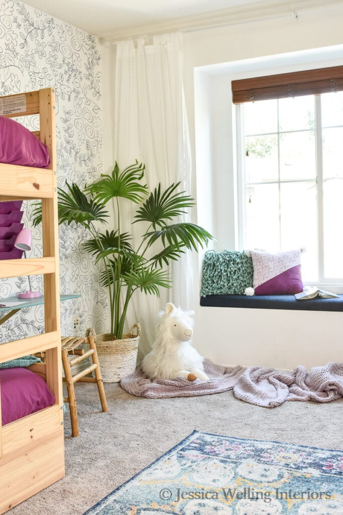 girls' bedroom with Ikea bunk beds, artificial plant, a faux wallpaper accent wall, and a stuffed alpaca