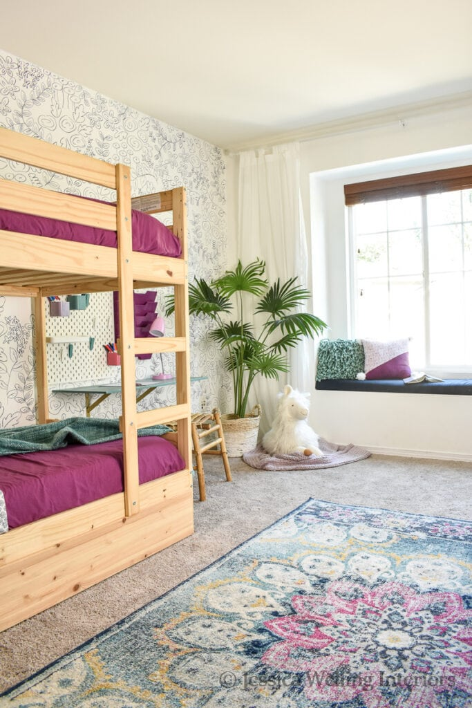 shared girls room with Boho decor including an oriental rug, Ikea bunk beds, a floating desk, a window seat, and a large stuffed llama
