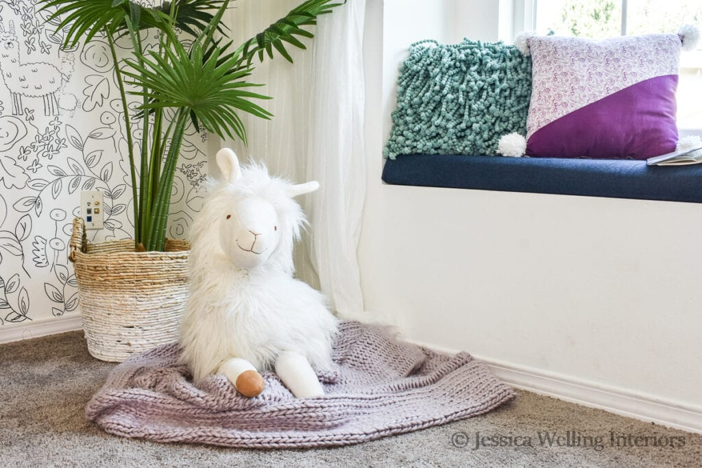 white stuffed llama sitting on the floor of a girls' bedroom with a purple blanket and a tall faux plant