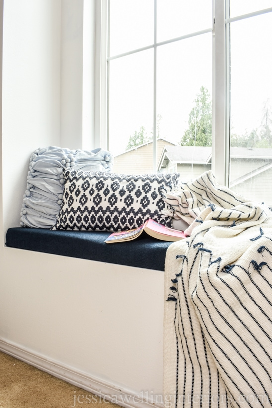 window seat with a DIY upholstered seat cushion, throw pillows, a blanket, and a book